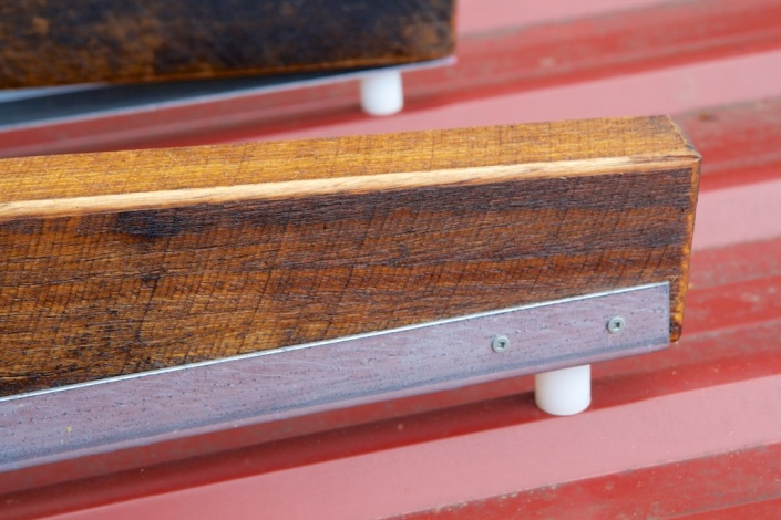 Detail of the top end of the sled, showing the wood, metal rail and nylon spacer.