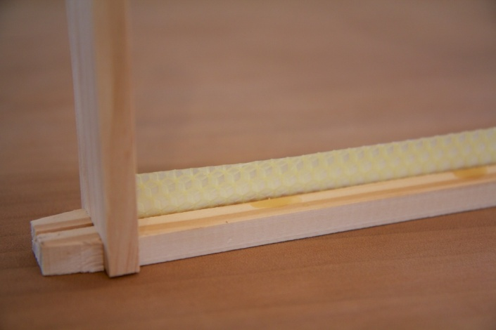 A starter strip of comb is 'glued' into the top bar, using melted wax.
